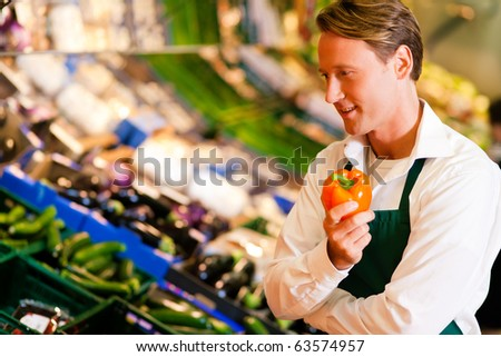 Shop assistant in a supermarket at the vegetable shelf checking the stuff for sale - stock photo