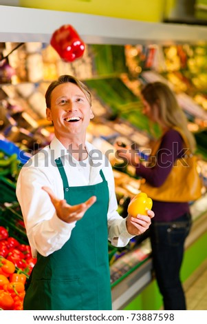 Shop assistant in a supermarket at the vegetable shelf; he is tossing a bell pepper - stock photo