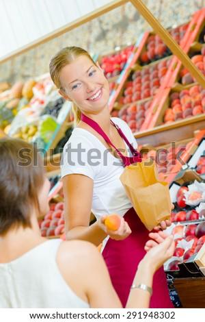Shop assistant on the fruit aisle - stock photo
