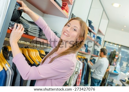 Shop assistant stacking shelves - stock photo