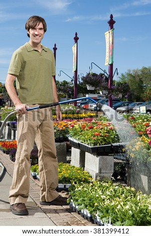 Shop assistant watering flowers