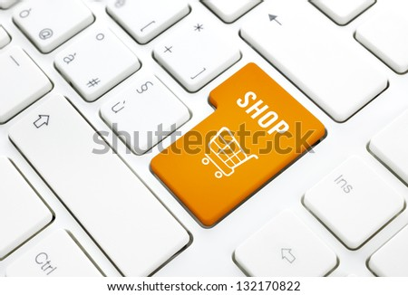 Shop business concept, Orange shopping cart button or key on white keyboard photography. - stock photo