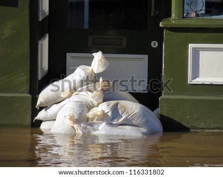 Shop doorway barricaded with sandbags in Tower Street, York, North Yorkshire. - stock photo