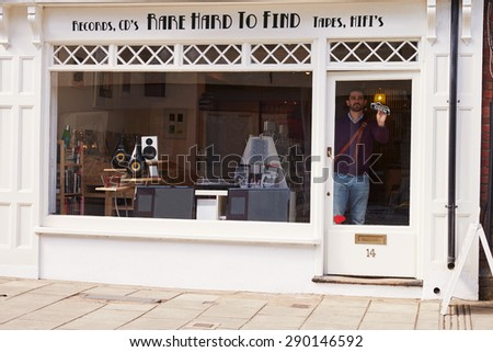 Shop owner opening up record, CD and hi-fi shop - stock photo