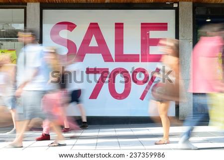 Shop sale sign, motion blurred pedestrians - stock photo