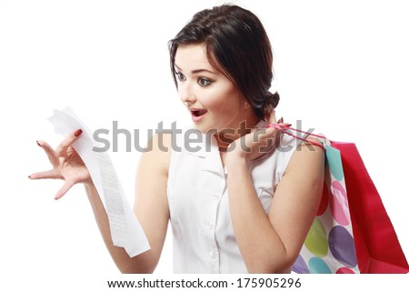 Shopaholic - Attractive brunette woman looking at her receipt - overspending - stock photo