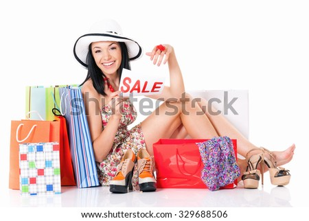 Shopaholic shopping woman with many shopping bags holding a signboard announcing a Sale, isolated on white background - stock photo