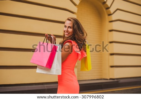shopaholic woman in bright dress beautiful young cheerful woman holding shopping bags and expressing positivity sale - stock photo