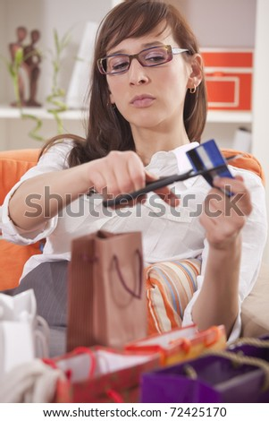 shopaholic woman with shopping bags cutting her credit card