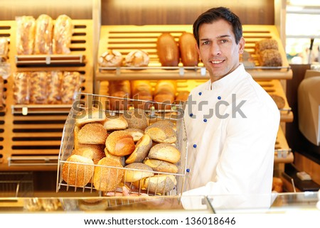 Shopkeeper presents a breadbasket to customer - stock photo