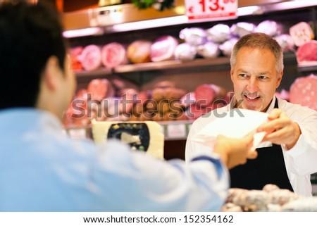 Shopkeeper serving a customer - stock photo