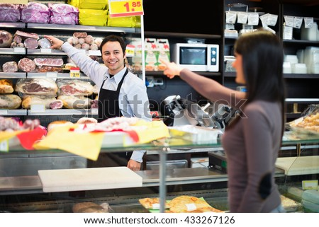 Shopkeeper serving a customer in his grocery store - stock photo