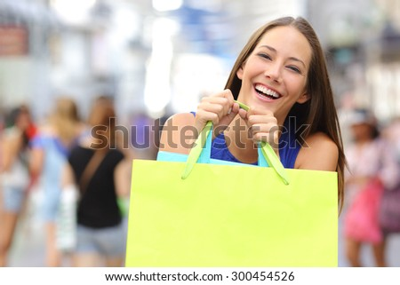 Shopper girl buying in a mall and holding a green shopping bag smiling to the camera - stock photo