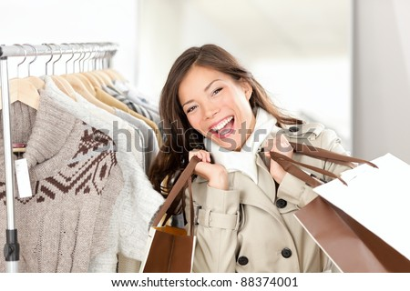 Shopper woman happy shopping buying clothes.  Joyful excited smiling woman - mixed race Caucasian / Chinese Asian female model holding shopping bags in trench coat inside in clothing store.
