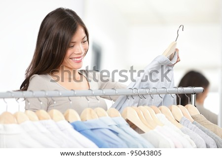 Shopper woman shopping clothes in clothing retail shop during sale.