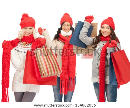 shopping and christmas concept - girls in red scarfs and hats with shopping bags - stock photo