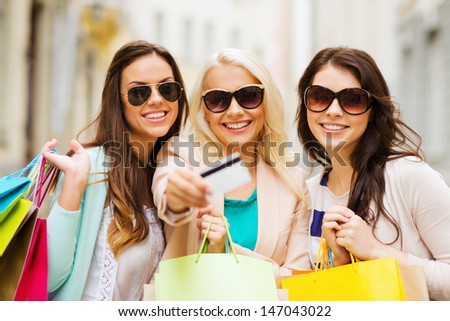 shopping and tourism concept - beautiful girls with shopping bags and credit card in ctiy - stock photo