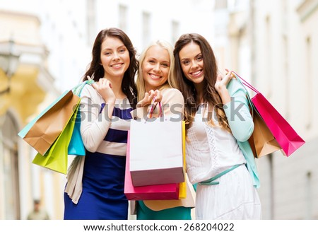 shopping and tourism concept - beautiful girls with shopping bags in city - stock photo