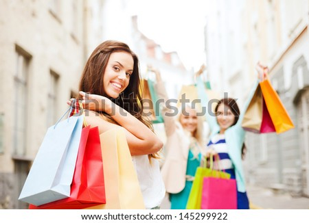 shopping and tourism concept - beautiful girls with shopping bags in ctiy