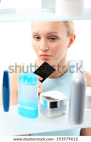 Shopping at the drugstore. Woman buying cosmetics in drugstore  A woman with a card club buys cosmetics  - stock photo