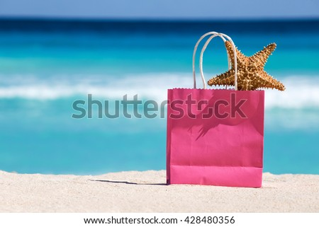 Shopping bag and starfish on sand against turquoise caribbean sea water. Tropical celebration on beach 