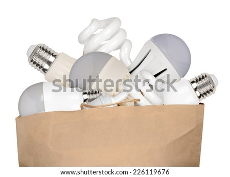 Shopping bag full of LED and fluorescent lamps isolated on white background - stock photo