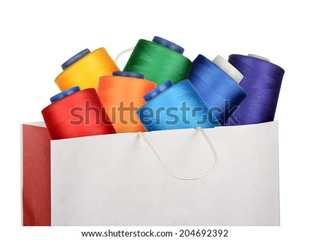 Shopping bag with sewing threads isolated on white background
