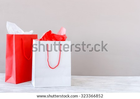 Shopping bags on table top against plain neutral background, christmas valentines birthday presents - stock photo