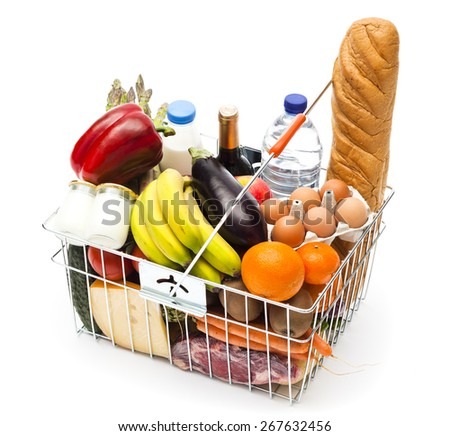 Shopping basket with assortment of food and drinks on white background - stock photo