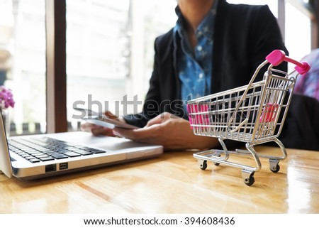 Shopping Cart and woman holding credit card and smart phone with laptop for a concept shopping online. - stock photo