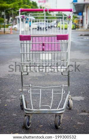 Shopping cart at supermarket parking lot - stock photo