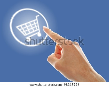 shopping cart button presses by a male hand on blue background - stock photo