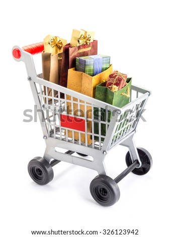 Shopping cart full of bags filled with presnts and gifts shot on white - stock photo