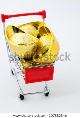 shopping cart full of Chinese gold ingot ornaments isolated on white. - stock photo
