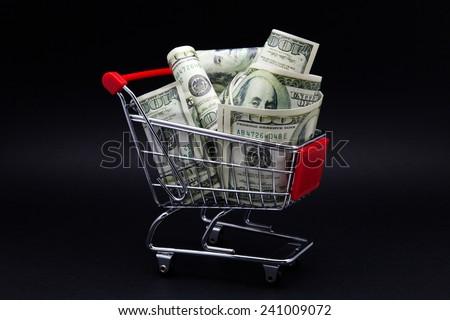 shopping cart full of dollar bills - stock photo