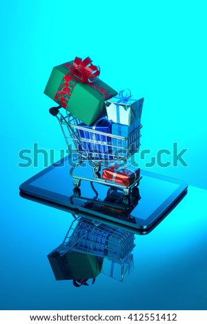 Shopping cart full of gift packages on tablet - stock photo