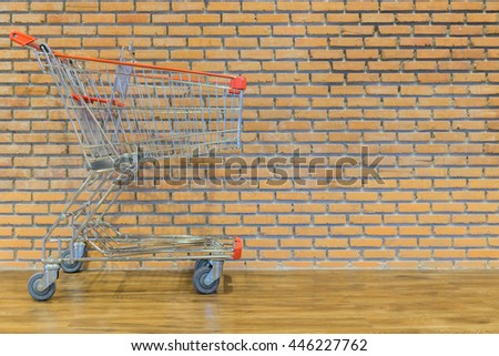 shopping cart in front of brick wall - stock photo