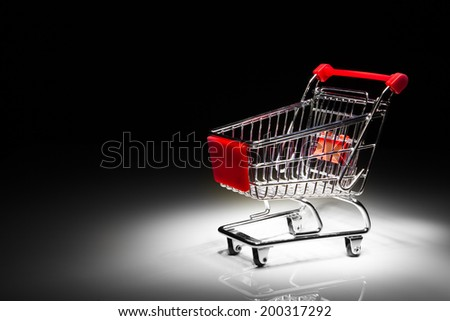 shopping cart on black background with copy-space - stock photo