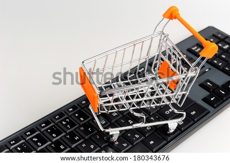 Shopping cart on black keyboard on gray background - stock photo