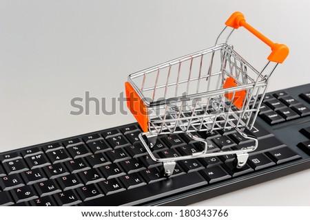 Shopping cart on black keyboard on gray background - stock photo