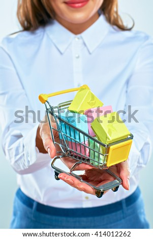 Shopping cart on female hand. Close up. Gifts.