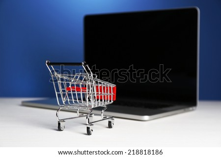 Shopping cart on laptop on table, on blue background - stock photo