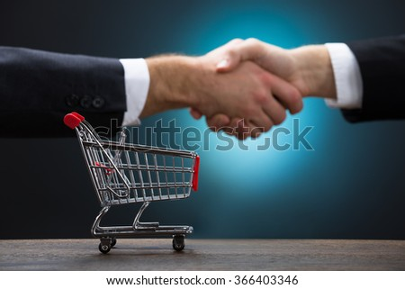 Shopping cart on table with businessmen shaking hands against blue background - stock photo