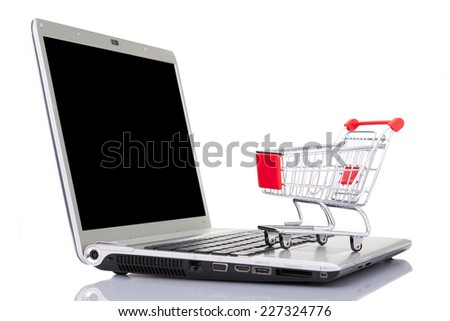Shopping cart over a laptop computer, isolated on white background