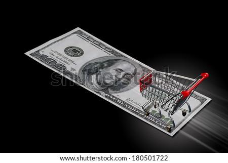 Shopping cart streaking across hundred dollar bill. - stock photo