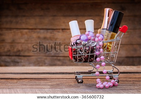 Shopping cart with cosmetics, beads, hair clip on old wood background. Toned image. - stock photo