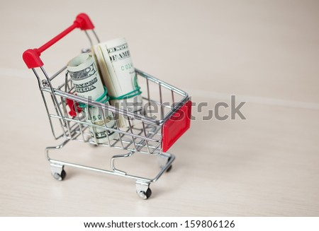 Shopping cart with dollars inside, on ceramic background - stock photo