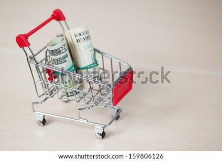 Shopping cart with dollars inside, on ceramic background - stock photo