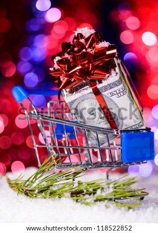 shopping cart with money against blurred lights on christmas tree - stock photo
