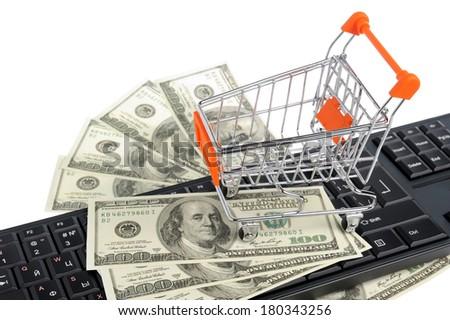 Shopping cart with money on black keyboard isolated on white background - stock photo